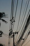 Alambres eléctricos y de teléfono en la luz oscuro de la puesta del sol Imágenes de archivo libres de regalías