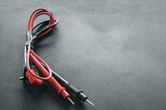 Alambres rojos y negros - + del voltímetro viejo para el voltaje de prueba en aparatos eléctricos imagen de archivo libre de regalías