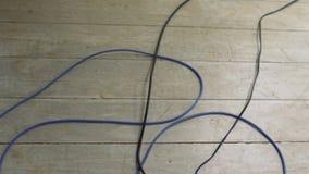 Alambres tapados al cable de extensión eléctrico, alambres en el piso, equipo eléctrico, red eléctrica almacen de video