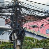 Alambres torcidos de las líneas eléctricas, caos de comunicaciones urbanas, paquete del cable fotos de archivo