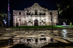 The Alamo in San Antonio, Texas during night after a rainfall with the building reflecting in water puddles.  stock photography