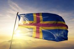 Aland region of Finland flag textile cloth fabric waving on the top sunrise mist fog. Beautiful stock photography