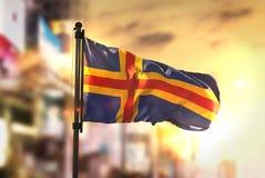 Aland wysp flaga Przeciw miasta Zamazanemu tłu Przy wschodów słońca półdupkami Obrazy Stock