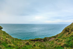 Alantic ocean and field of green grass, Ireland Europe Royalty Free Stock Images