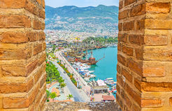 Alanya between the battlements of Red Tower. ALANYA, TURKEY - MAY 9, 2017: The view on the harbor of Alanya with numerous tourist ships and motor boats from the Royalty Free Stock Image