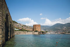 Alanya medieval castle which includes Red Tower Shipyard by sea. Castle walls Red Tower and Shipyard in Alanya in Turkey near harbor on Mediterranean sea coast Stock Photos