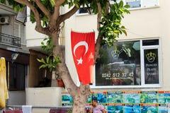Alanya, Turcja, Lipiec 2017: turecki chorągwiany obwieszenie na drzewnym dobrze na ulicie Fotografia Stock