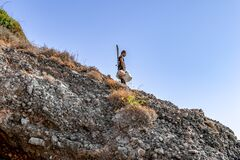 Turkish fisherman with fishing rods and buckets stands on a rock and looks down. A man descends