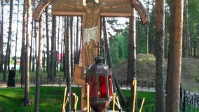 Candles near cross with crucifix in place of execution of Elizabeth Feodorovna. Alapaevsk, Russia - 17 July 2012: Candles near cross with crucifix in place of stock footage