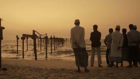 Alappuzha beach, south india, men contemplating sea at sunset stock footage