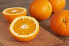 Alaranjado Corte a laranja em uma placa de corte de madeira fotografia de stock royalty free