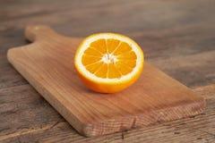 Alaranjado Corte a laranja em uma placa de corte de madeira foto de stock