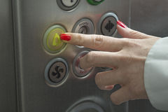 Alarm button. Female hand pressing the alarm button in the elevator royalty free stock photos