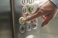 Alarm button. Hand pressing the alarm button in the elevator royalty free stock photo
