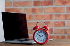 Alarm clcok and laptop Stock Photography