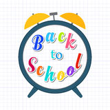 Alarm cloack with text yellow background Back to school. Stock Photos