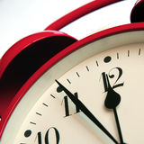 Alarm clock 1. Red retro-style alarm clock showing five minutes to twelve Royalty Free Stock Photo