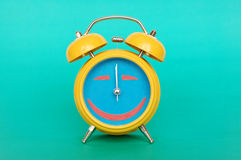 Alarm clock. Yellow alarm clock close up, smile Stock Photos
