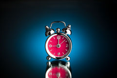 Alarm clock. With pink clock dial on blue background Royalty Free Stock Photo