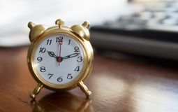 Alarm clock. Golden alarm clock on dark office table Stock Images