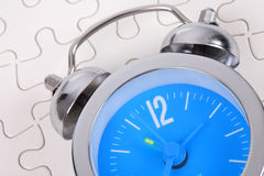 Alarm clock. With white puzzle background Stock Photos
