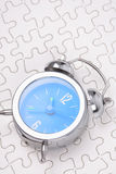 Alarm clock. With white puzzle background Royalty Free Stock Images