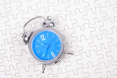 Alarm clock. With white puzzle background Royalty Free Stock Photo