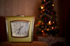 Alarm clock. The alarm clock costs in the foreground and a New Year tree on a background Stock Image