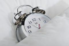 Alarm clock. Classical alarm clock sleeping on bed until noon Stock Photo