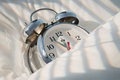 Alarm clock. Classical alarm clock sleeping on bed until noon with sunlight Royalty Free Stock Photography