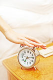 Alarm clock. Woman hand turning off alarm clock Royalty Free Stock Images