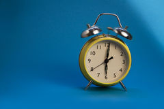 Alarm clock. A bright yellow old fashioned style alarm clock on blue background with bell ringing Stock Photo