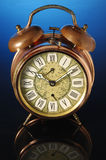 Alarm clock. Old fashioned alarm clock on a blue background Royalty Free Stock Image