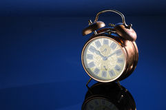 Alarm clock. Old fashioned alarm clock on a blue background Stock Image