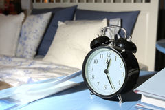 Alarm clock. On night table at bed royalty free stock image