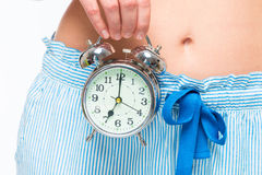 Alarm clock at abdominal level in female hands closeup Royalty Free Stock Images