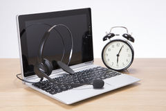 Alarm clock alongside a laptop and headset Royalty Free Stock Images