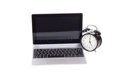 Alarm clock alongside an open laptop computer Stock Photo