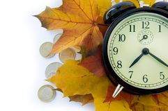 Alarm clock, autumn leafs and coins. Royalty Free Stock Photos