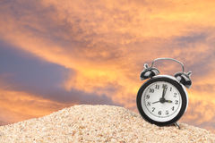 Alarm clock on beach. And orange sunset sky Stock Photo