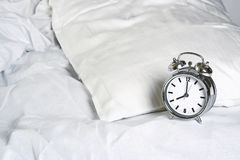 Alarm clock on the bed Stock Photo