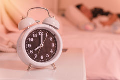 alarm clock on the bed in bedroom, retro style Stock Photography