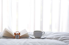 Alarm clock on bed with coffee and book in morning. With sun light Royalty Free Stock Image