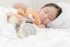 Alarm clock on bed and girl sleep on background. Alarm clock on bed and girl sleep and put hands off her ears on background, healthcare concept Stock Image