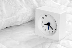 Alarm clock on bed. Royalty Free Stock Images
