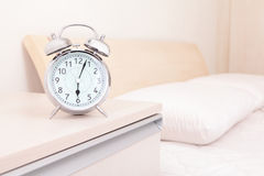 Alarm clock and bed Royalty Free Stock Images