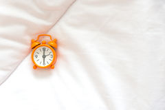 Alarm clock on bed Stock Photos