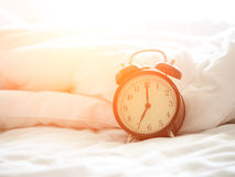 Alarm clock on bed in morning. With sun light Stock Photography
