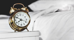 Alarm clock and bed Stock Image