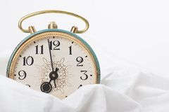 Alarm clock on the bed Royalty Free Stock Photo